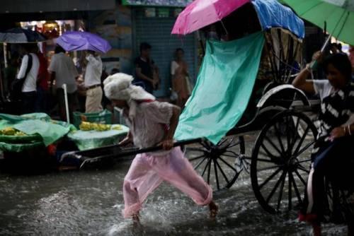 Un uomo con il risciò per le strade allagate in India