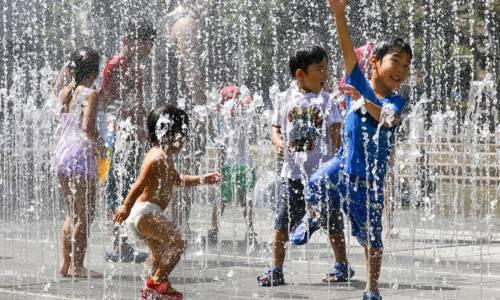 Un gruppo di bambini gioca fra i getti d'acqua in un parco vicino a Nerima,Tokyo